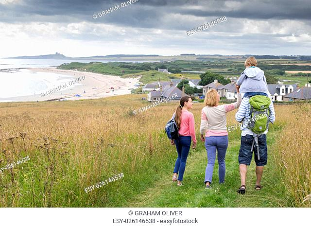 A fmaily of four are walking along the sand dunes. The little boy is getting carried on his fathers shoulders