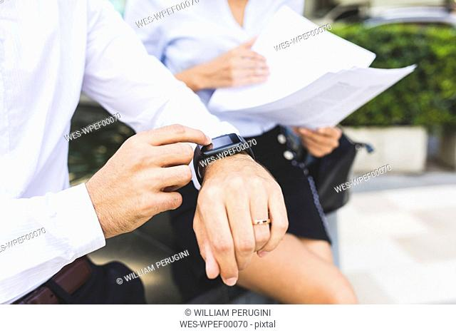 Businessman with smartwatch and businesswoman with documents in the city