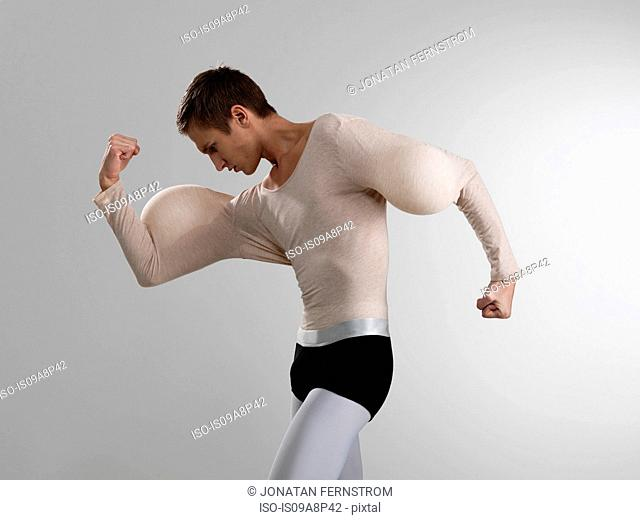 Man flexing muscles with balloons in sleeves
