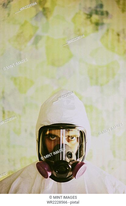 Portrait of a man wearing breathing apparatus and a protective clean suit with a covered head