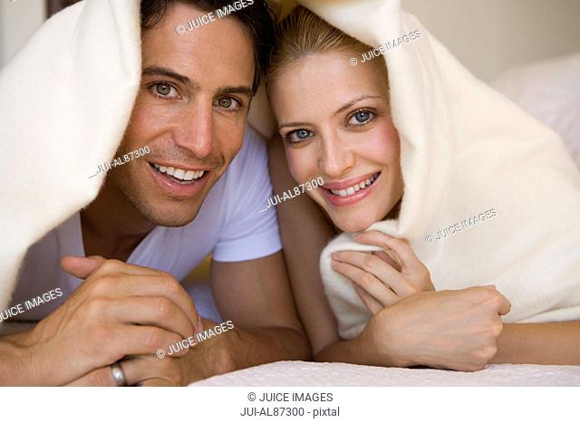 Couple laying under blanket