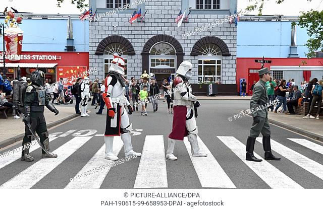 15 June 2019, North Rhine-Westphalia, Bottrop: Cosplayer disguised as Star Wars figures walk over a zebra crossing during the 2nd Cosplay Day in the Movie Park