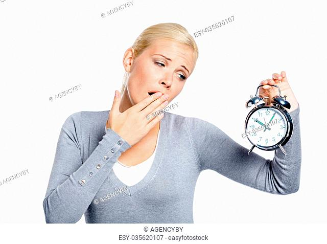 Yawning woman in grey pullover with alarm clock, isolated on white
