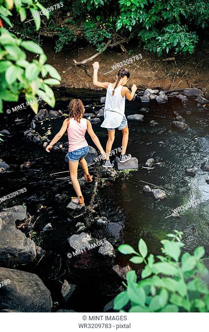 Girls using stones to cross creek