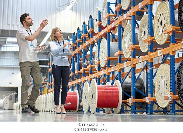 Male and female supervisors checking inventory in fiber optics factory