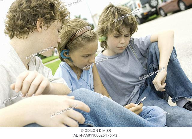 Children sitting in street, one with mp3 player
