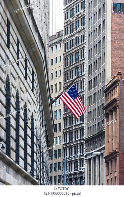 USA, New York State, New York City, Manhattan, Wall Street, American flag among skyscrapers