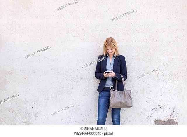Smiling blond businesswoman standing in front of wall looking at smartphone