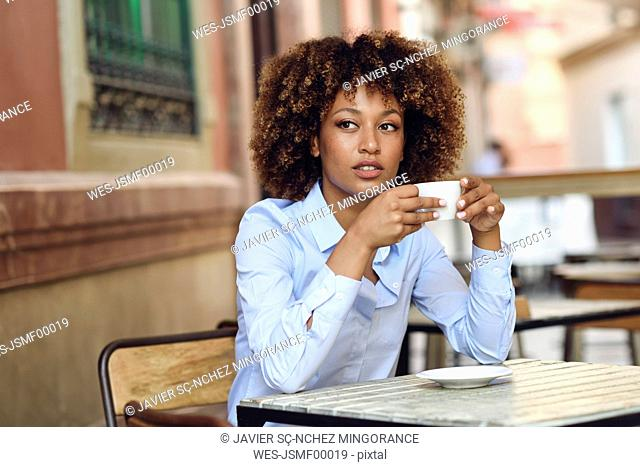 Woman with afro hairstyle sitting in outdoor cafe drinking coffee