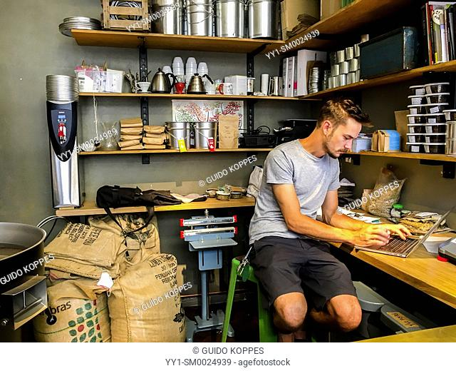 Berlin, Germany. Young, male employee working inside the coffee burn section of a little restaurant and coffeeplace. Fresh Coffee Beans are burned by him