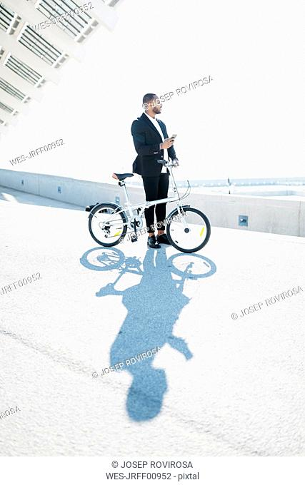 Businessman with bicycle holding cell phone
