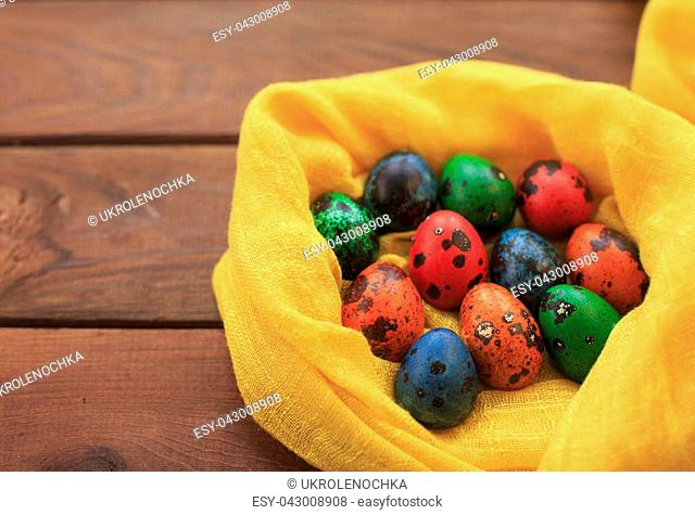Easter background with colorful painted quail Easter eggs on wood background in a nest. Copy space, vintage style, top view