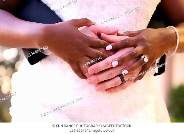 multi cultural couple embracing - close up on hands
