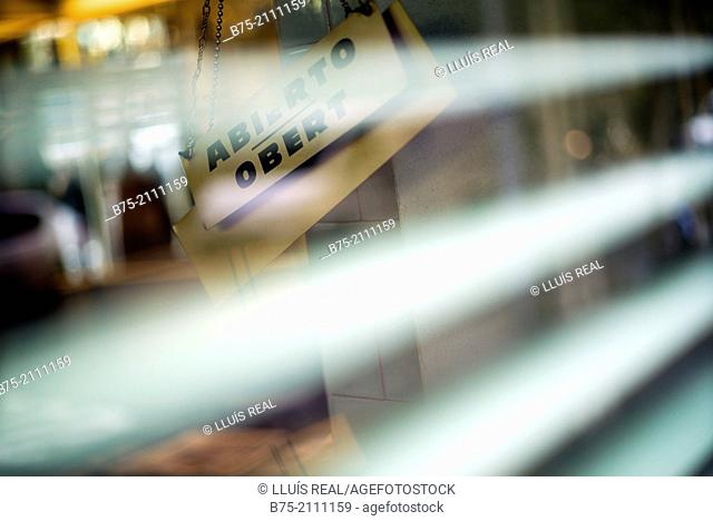 Ad in a door shop with the words Abierto - Obert, seen from a blinds of a shop in Barcelona, Spain, Europe