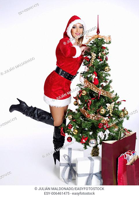 Young woman dressed in Mama Claus with some shopping and gifts