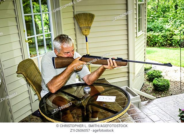Man sitting on the porch of his house in Port Huron Michigan firing a rifle at a target
