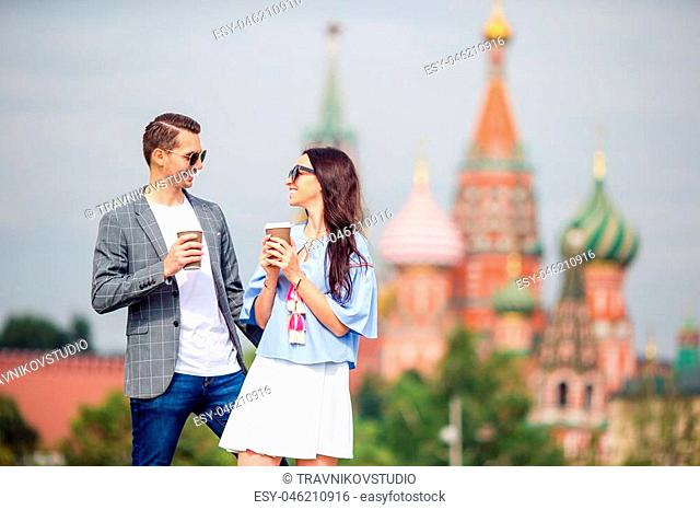 Young dating couple in love walking in city. Portrait of a happy romantic couple with coffee walking outdoors in Moscow city