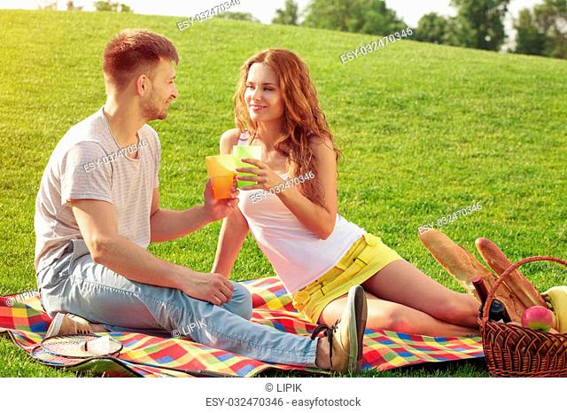 Couple in park on picnic. Young man and woman drinking tasteful cocktails and sitting on carpet