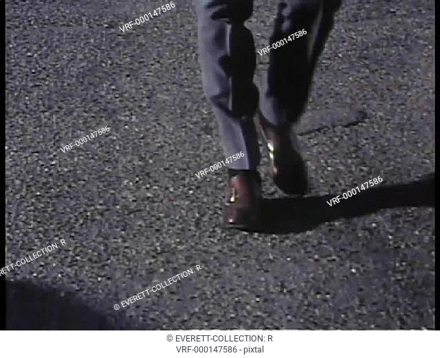 Medium shot of person's feet and legs walking on asphalt