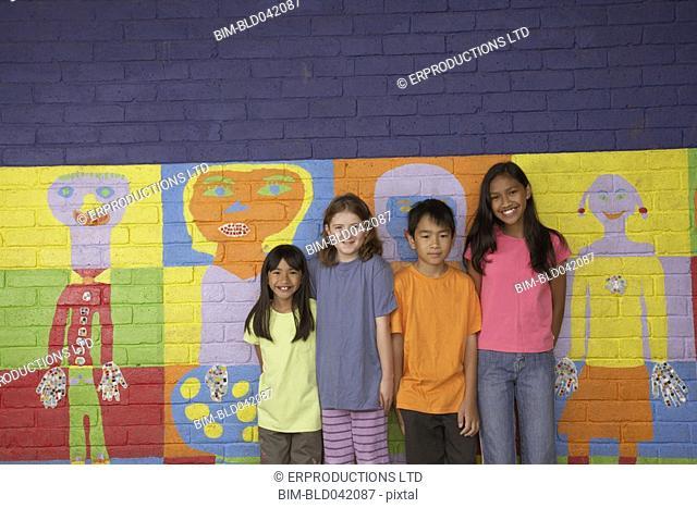 Multi-ethnic children in front of mural