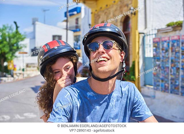 Young couple enjoying moped ride together. Hersonissos, Crete, Greece