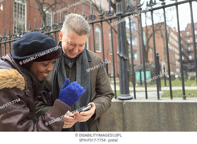 Couple looking at pictures on a cell phone along Tremont Street and The Granary Burying Ground Historic site, Boston, Suffolk County, Massachusetts, USA