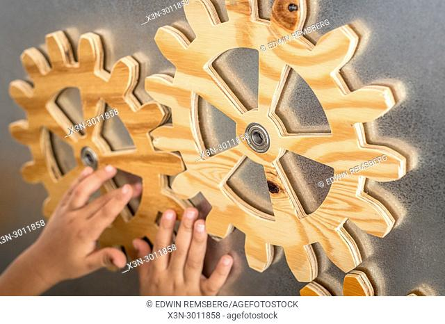 Child hands aligning wooden gears together on board, Silver Spring, Maryland. USA