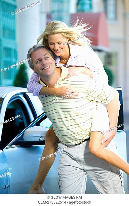 Man giving piggyback ride to his wife and smiling, Biltmore Hotel, Coral Gables, Florida, USA
