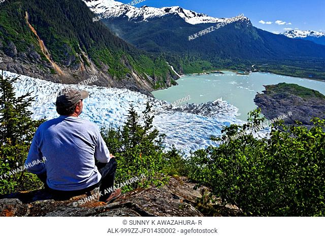 A male hiker looking down onto Mendenhall Glacier and Mendenhall Lake from West Glacier Trail, Juneau, Southeast Alaska, Summer
