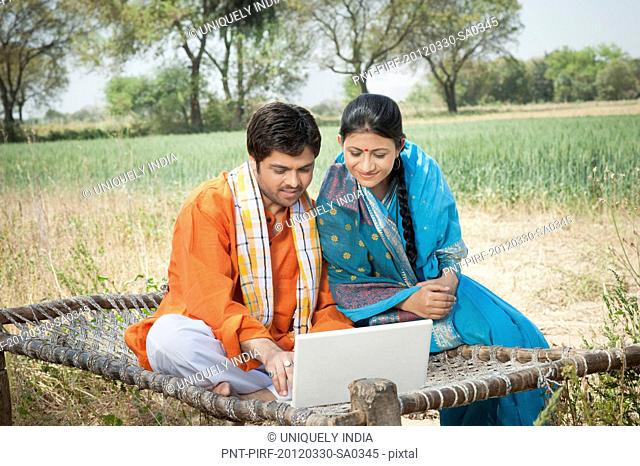 Rural couple using a laptop, Sohna, Haryana, India