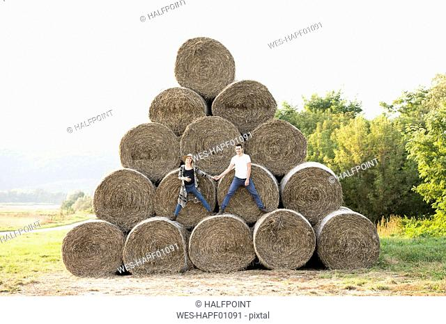 Expectant parents standing on bales of straw