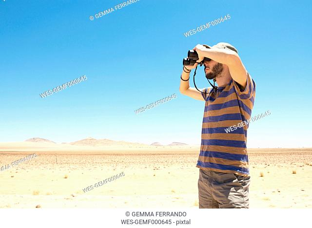 Namibia, Namib desert, man with hat using binoculars to look away