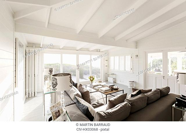 Sunny luxury home showcase living room with white wood beam vaulted ceiling