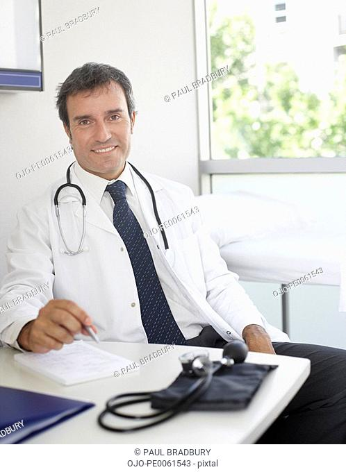 Doctor sitting in office by large window smiling