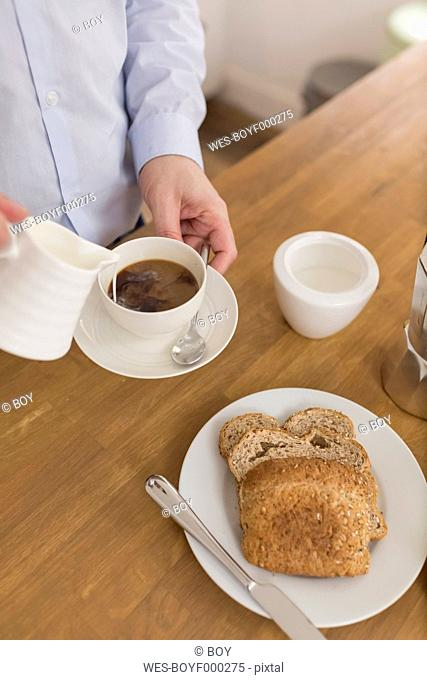 Man pouring milk into coffee cup at breakfast table, partial view
