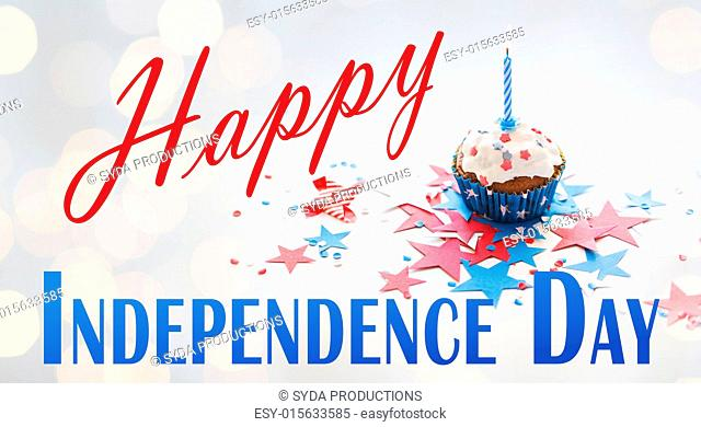 happy independence day, celebration, patriotism and holidays concept - close up of cupcake or muffin with burning candle and stars cofetti decoration on table...