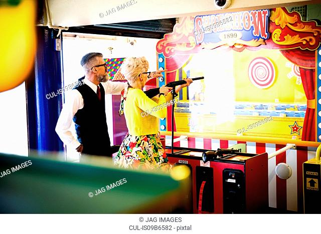 Quirky couple enjoying shooting gallery in amusement arcade, Bournemouth, England