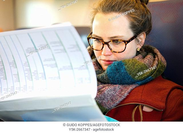 Utrecht, Netherlands. Female brunette woman reading the planning of a project, while commuting by intercity train
