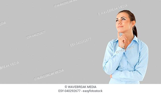 Woman thinking in front of grey background