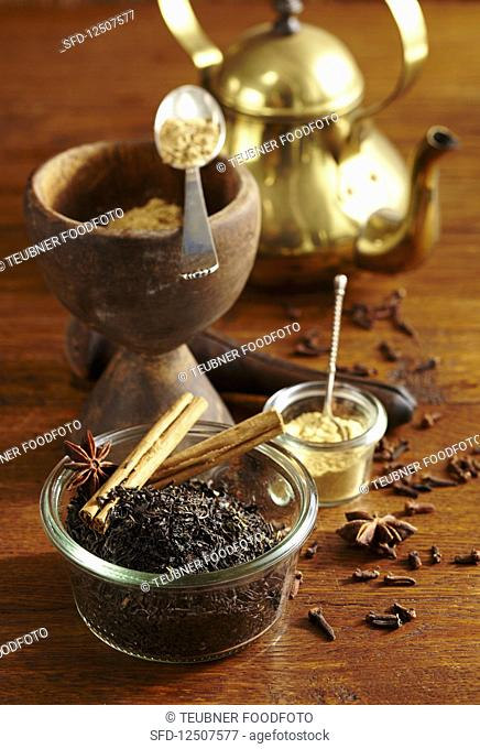 an arrangement of spices with a golden teapot