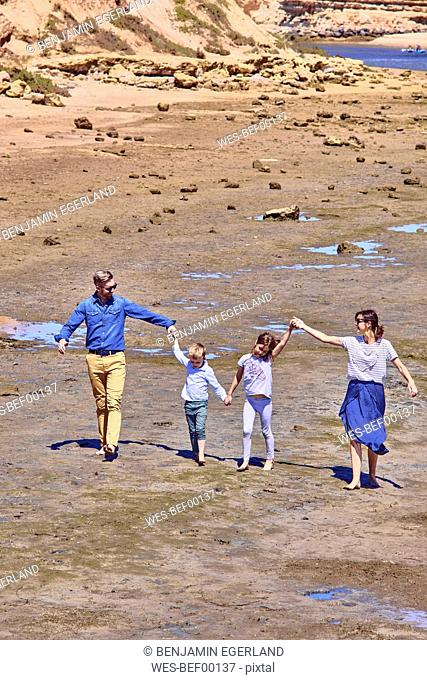 Australia, Adelaide, Onkaparinga River, happy family walking together hands in hands at beach