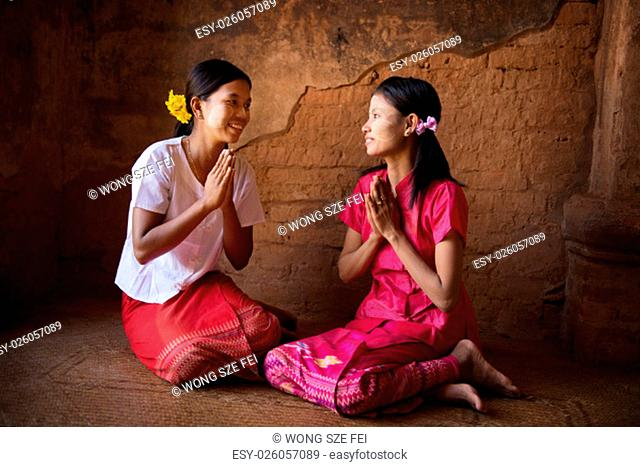 Two young Myanmar girl in a traditional welcoming gesture, sitting inside temple