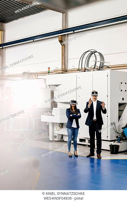 Businessman an woman in high tech enterprise, using VR glasses