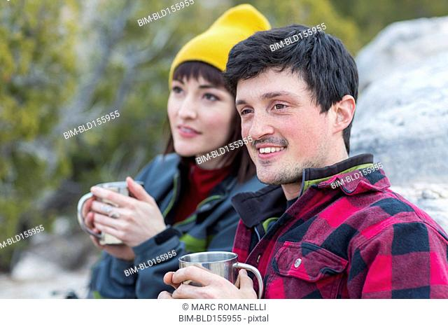 Couple sharing coffee on rock formations