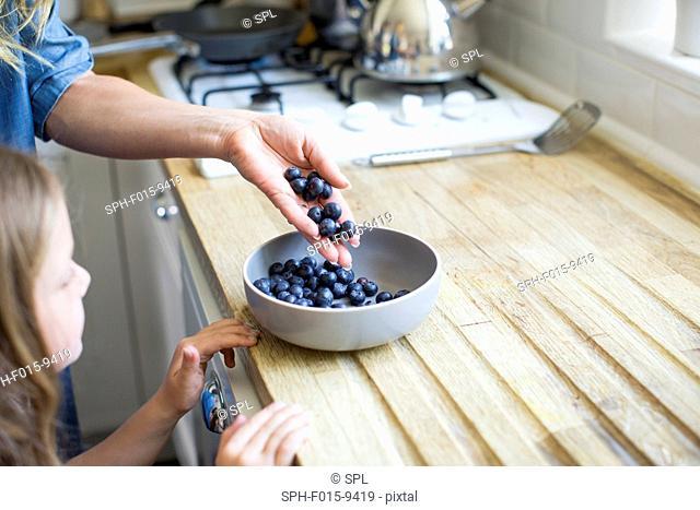 MODEL RELEASED. Girl looking at bowl of fresh blueberries