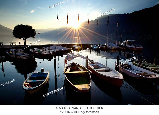 Harbour in sunset over an alpine lake with mountains and sunbeams