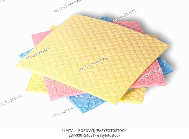 Multicolored sponges for dishwashing in a chaotic order isolated on white background