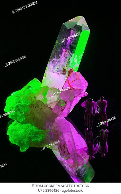 Crystal quartz mineral stone with lighting effects, mini figures and mirror in studio setting
