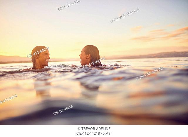Young couple swimming in ocean at sunset