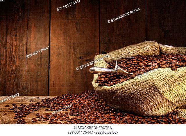 Burlap sack of coffee beans against dark wood background